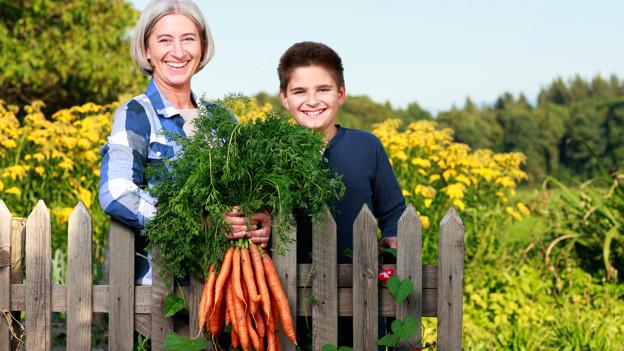 Eine Oma und ihr Enkelkind zeigen in ihrem Garten einen Bund frisch geernteter Karotten.