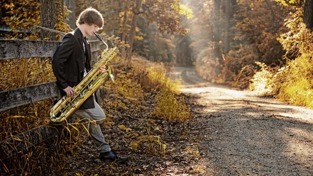 Ein junge Mann spielt auf einem Weg in einem herbstlichen Wald Saxofon.