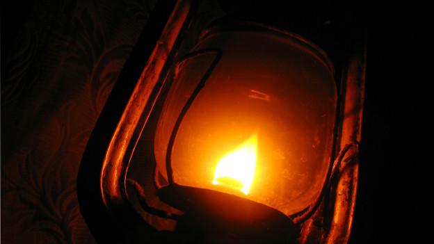 Grossaufnahme einer Öllampe mit brennendem Docht.