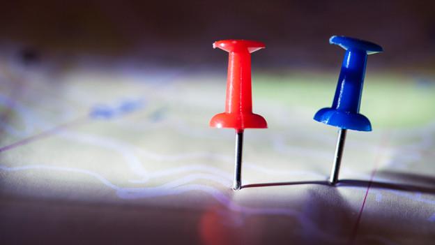 Eine rote und eine blaue Stecknadel auf einer verschwommenen Landkarte.
