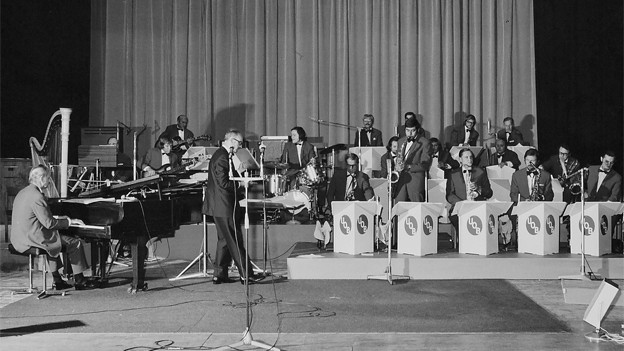 Schwarz-Weiss Fotografie vom Unterhaltungsorchester während eines Auftritts.