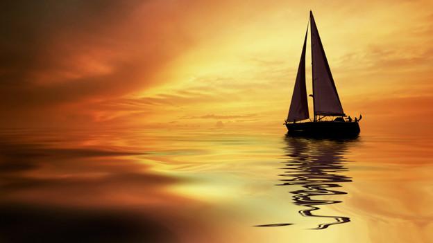 Ein einsames Segelboot im goldenen Licht eines Sonnenuntergangs.