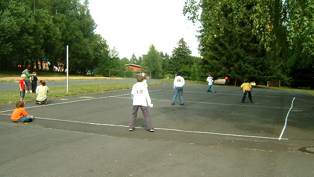 Kinder spielen Völkerball auf Teerplatz.
