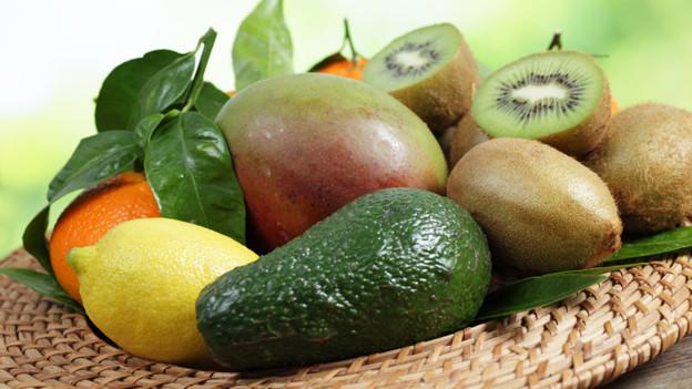 Ein Korb voller südlicher Früchte: Orange, Zitrone, Avocado, Mango und Kiwi.