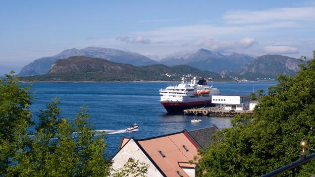 Grosses, weisses Passagierschiff inmitten Norwegischem Fjord.