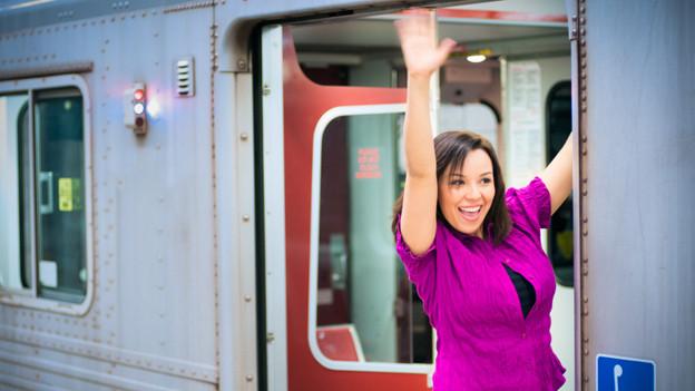 Eine Frau mit einer pinkfarbenen Bluse steht auf dem Trittbrett eines U-Bahn-Waggons und winkt.