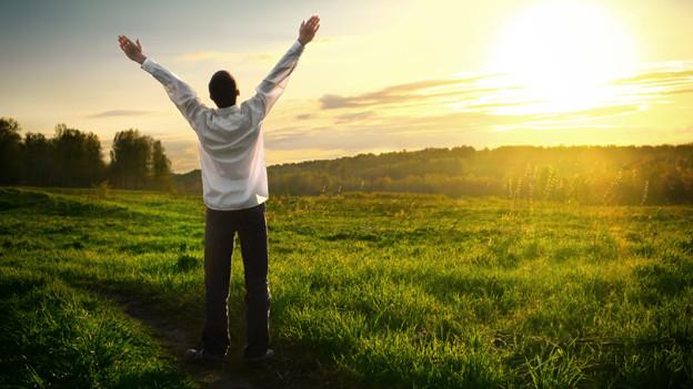 Ein Mann streckt bei Sonnenaufgang glücklich seine Arme in die Höhe.