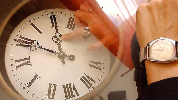 Frau richtet den Uhrzeiger einer Wanduhr nach der neuen Uhrzeit.