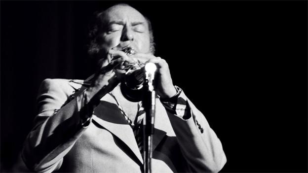 Schwarz-Weiss Fotografie von Woodly Herman, der bei einem Auftritt Trompete spielt.