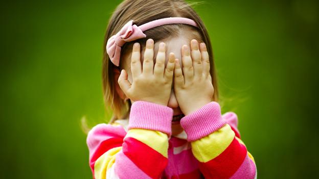 Ein kleines Mädchen hält sich die Hände vor die Augen.