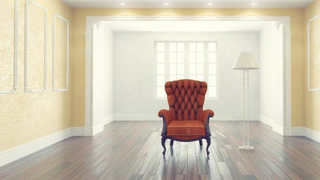 Ein rotes Fauteuil (Chesterfield Stil) steht vor hell erleuchtetem Fenster in Zimmer mit hohen Wänden.