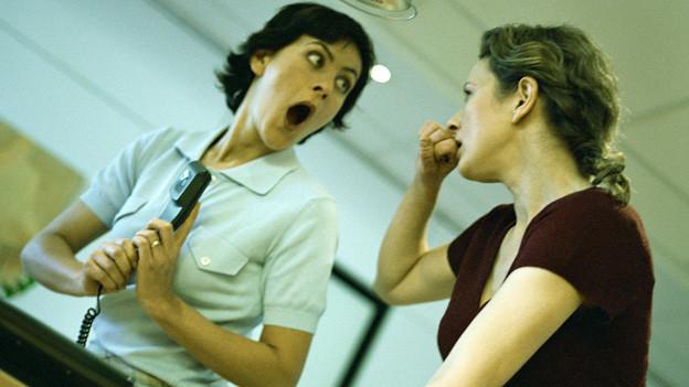 Zwei Damen sind offensichtlich schockiert über einen Telefonanruf.