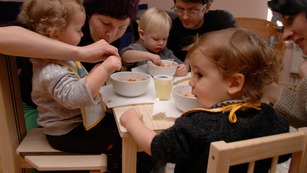 Kleine Kinder sitzen am Tisch und werden von ihren Müttern gefüttert.