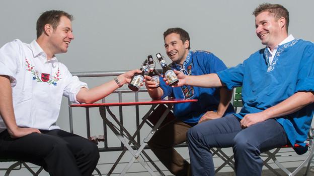 Die drei Musikanten sitzen auf der Terrasse eines Restaurants und prosten sich mit je einer Flasche Bier zu.