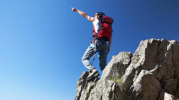 Ein Bergsteiger steht auf einem Felsen und zeigt auf einen höher gelegenen Gipfel.