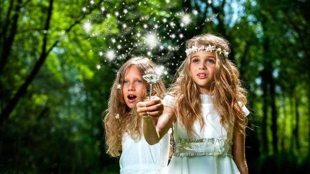Zwei elfenhafte Mädchen in weissen Kleidern zaubern in einem Wald mit ihrem Zauberstab Sterne herbei.
