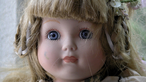 Gesicht einer alten Puppe mit grossen blauen Augen und blonden Haaren.