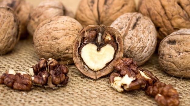 Viele Baumnüsse auf einem Jutesack. Von einer geöffneten sieht man die eine Hälfte, davor liegen ein paar Nüsse ohne Schale.