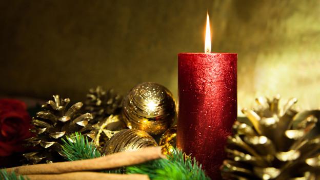 Gold bemalte Föhrenzapfen, goldige Weihnachtskugel und eine grosse rote, brennende Kerze.