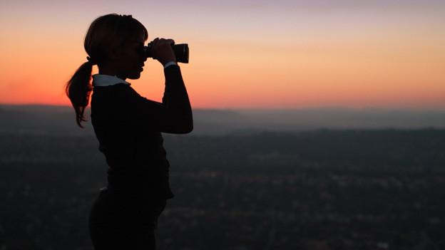 Eine junge Frau blickt bei Sonnenuntergang mit einem Feldstecher auf ein weit entferntes Ziel.