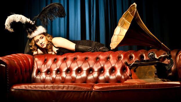Eine Frau mit Federschmuck liegt auf der Lehne eines alten roten Ledersofas und hört Musik, die aus dem grossen Trichter eines alten Grammophons ertönt.