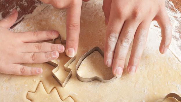 Eine Frauenhand und eine Kinderhand drücken einen Tannen- und eine Herzform zum Ausstechen in den Teig.