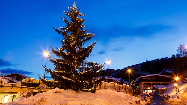 Ein grosser Weihnachtsbaum steht auf einem kleinen Hügel neben der Strasse, die durch ein verschneites Dorf führt.