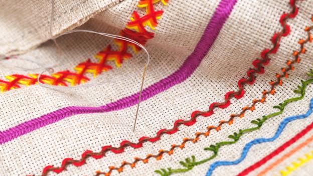 Eine feine Nadel steckt in einem Stück Stoff, auf den in verschiedenen Farben verschiedene Muster gestickt sind.