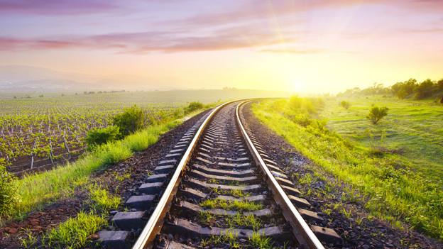 Eine Bahnschiene verläuft in eine Kurve, die vom Licht eines Sonnenuntergangs beleuchtet wird.