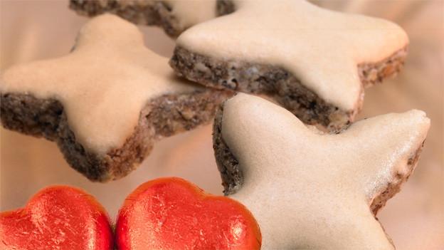 Zwei in rotes Papier gewickelte Schokoladenherzen und vier Zimtsterne mit weissem Zuckerguss.