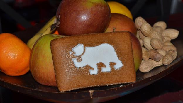 Ein Lebkuchen mit einem Bär aus Zuckerguss liegt vor ein paar Früchten in einer Fruchtschale.
