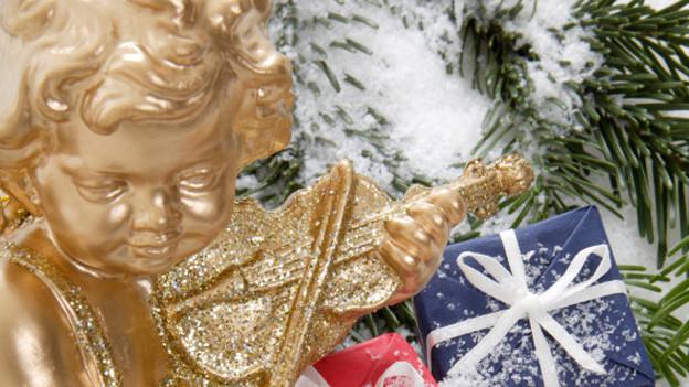 Ein kleiner goldener Engel mit Harfe vor ein paar kleinen Weihnachtsgeschenken.