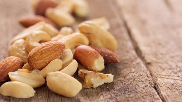 Verschiedene Nüsse auf einem Küchentisch.