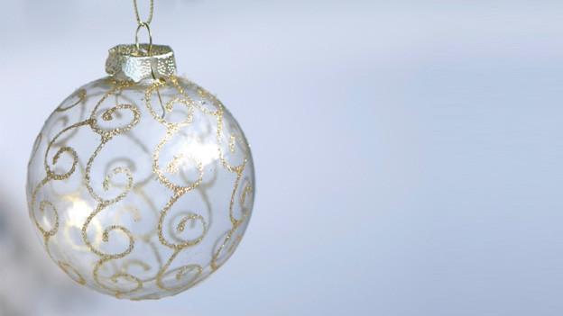Eine Weihnachtskugel aus Glas mit feinen goldenen Verzierungen.