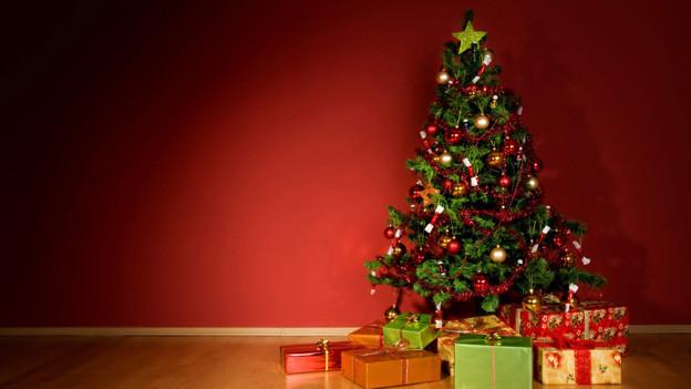 Ein reich dekorierter Weihnachtsbaum vor einer roten Wand. Davor liegen viele Geschenkpakete.