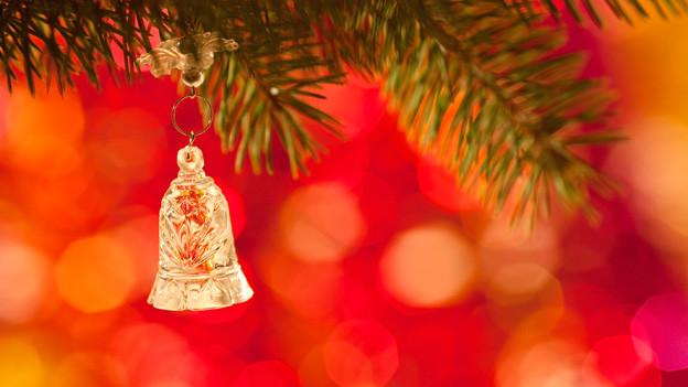 Eine zarte Glocke aus Glas hängt an einem Tannenzweig.