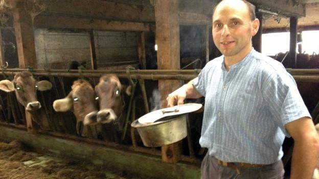 Niklaus Dobler steht mit einer Pfanne Weihrauch im Stall und wird von drei Kühen neugierig beobachtet.