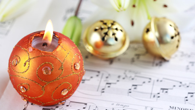 Eine runde Kerze und ein paar goldene Weihnachtsschellen auf einem Notenblatt.