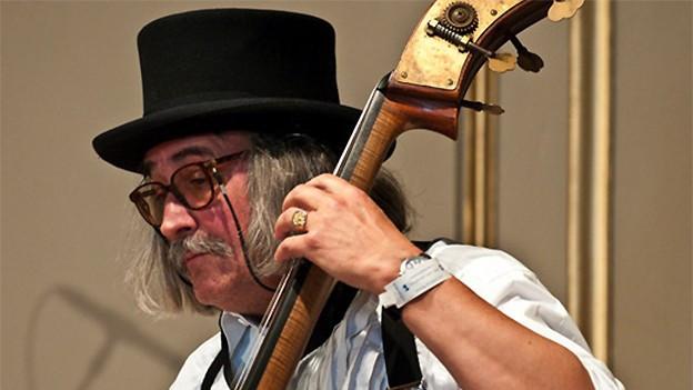 Der Musiker trägt einen Zylinder und spielt Kontrabass.