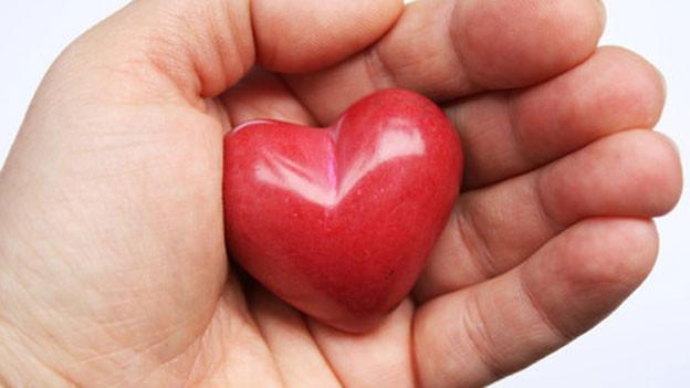 Hand mit rotem Herz aus Stein.