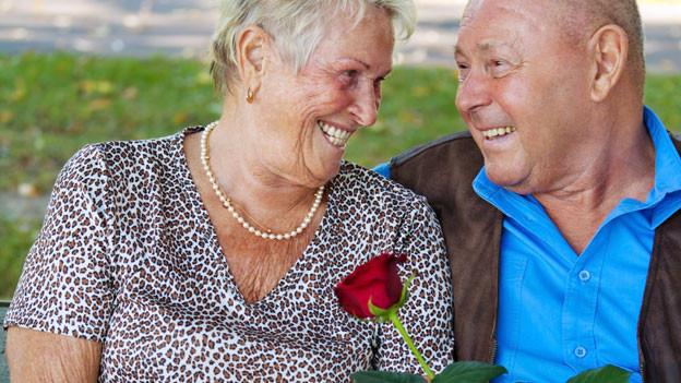 Älteres Paar auf Wiese lächelt sich verliebt zu. Er überreicht ihr dabei eine rote Rose.