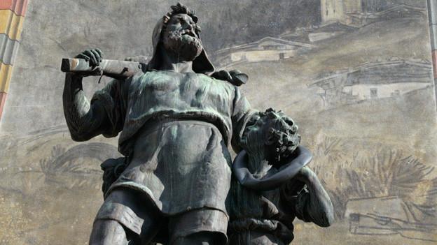 Tell, mit Armbrust bewaffnet, legt seinen Arm um seines Sohns Schulter.