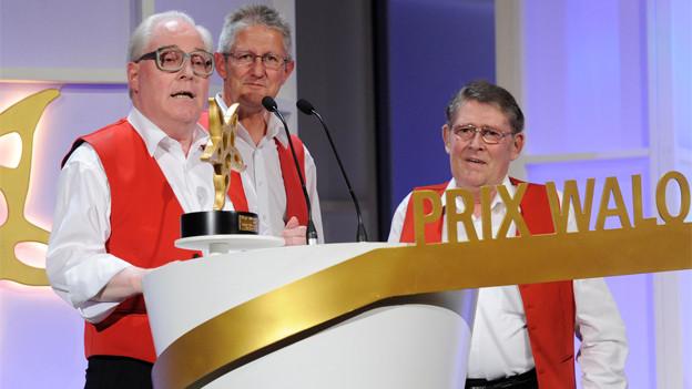 Drei Musiker der erfolgreichen Kapelle nach der Preisübergabe am Rednerpult im Kongresshaus Zürich.