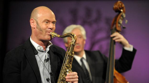 Während TV-Sendung spielt Pius Saxophon.