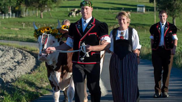 Ein stimmungsvoller Bild mit einem königlichen Einmarsch. Muni, Schwingerkönig, dessen Freundin und ein Begleiter auf einer Dorfstrasse.