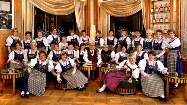 Gruppenbild mit den Jodlerinnen und dem Dirigenten. Sie sitzen in ihren schönen Trachten in einem schmucken Saal.