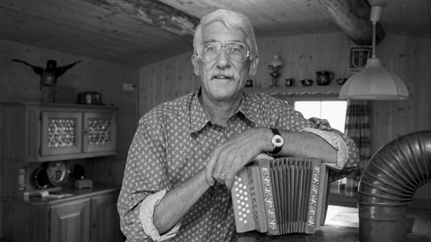 Schwarz-Weiss Fotografie von Peter Zinsli mit Schwyzerörgeli in seinem Wohnzimmer.