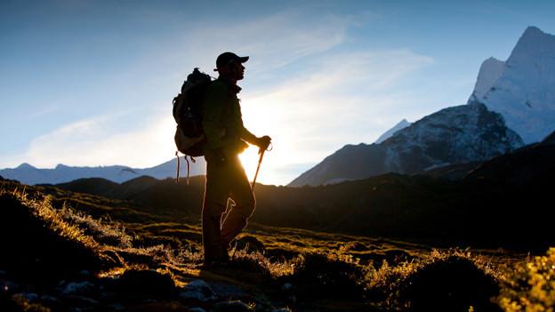 Ein Wanderer in den Bergen vor dem Sonnenlicht.