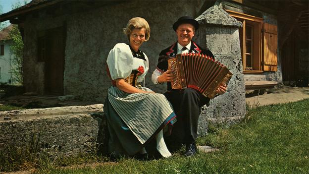 Heidi und Ernst Sommer sitzen in ihrer Tracht auf einer Mauer. Ernst Sommer spielt Schwyzerörgeli.