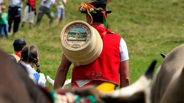 Ein Toggenburger Senn in schöner Tracht trägt den Fahreinser mit dem bemalten Boden auf dem Rücken.